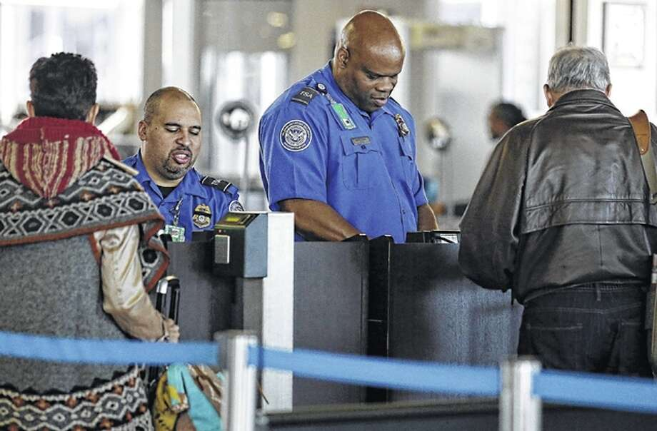Transportation Security Administration agents check traveler identifications at a security checkpoint area at O'Hare International Airport in Chicago. Those who don't have the latest driver's licenses will have a two-year reprieve before their IDs are rejected at airport security checkpoints. Many travelers had been worried that the Transportation Security Administration would penalize them because of a federal law requiring the more-stringent IDs at the start of this year. Photo: Nam Y. Huh | AP