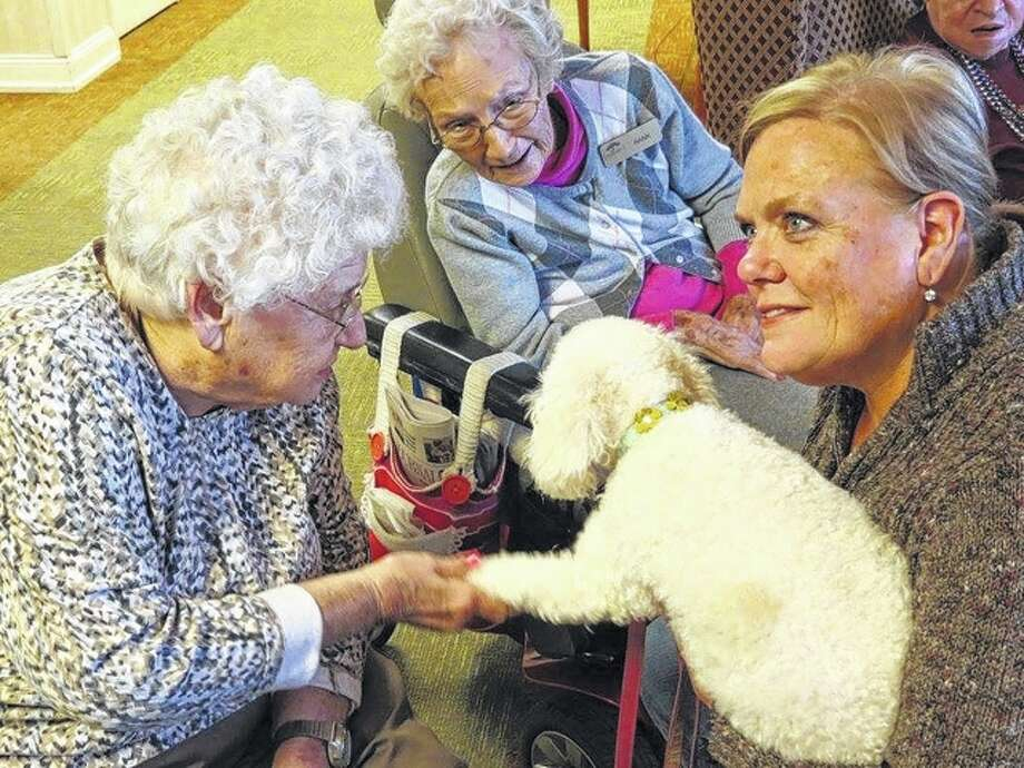 Bark Park volunteer Jan Tiffin holds her dog, Paisley, during a visit Saturday to Knollwood Retirement Village in Jacksonville.
