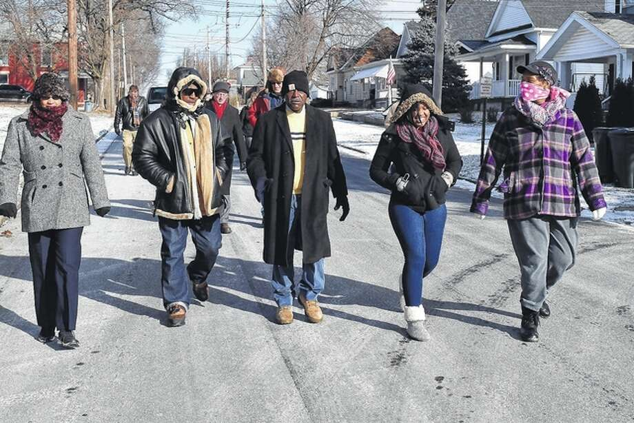 About two dozen people took part Monday in the Dr. Martin Luther King Jr. Day march in Jacksonville. Participants, including King Day organizer Jackie Rogers (center), walked down South Church Street toward the King monument in Community Park.