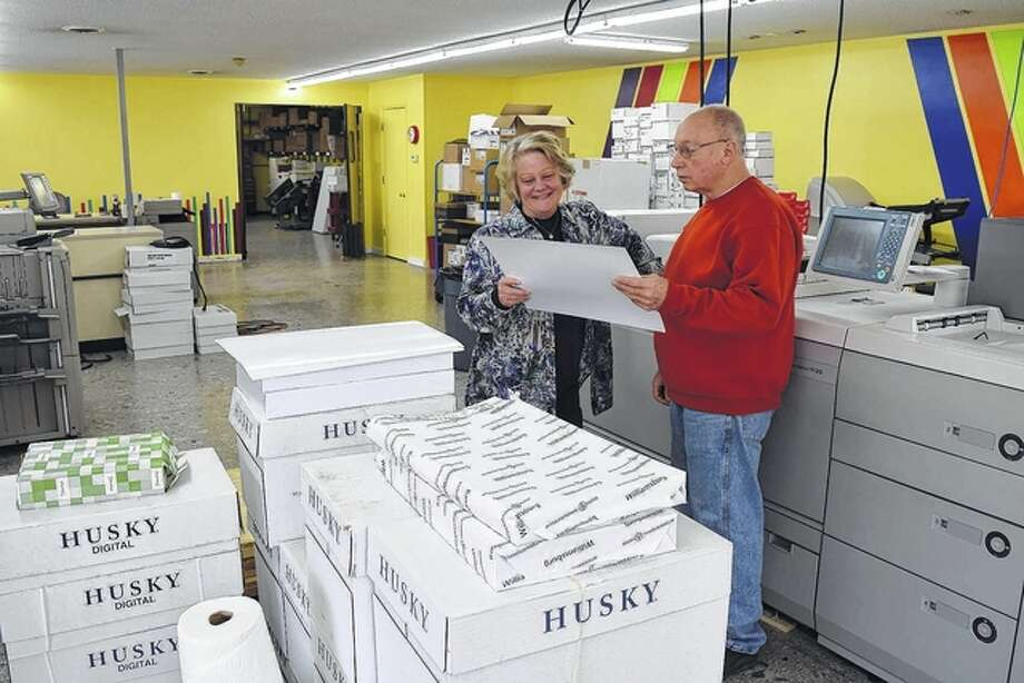 Faith Printing co-owners and -operators JaNell and James Lyle look over a book cover at their new Jacksonville printing shop at 880 S. Main St., which will open Monday. Photo: Greg Olson | Journal-Courier