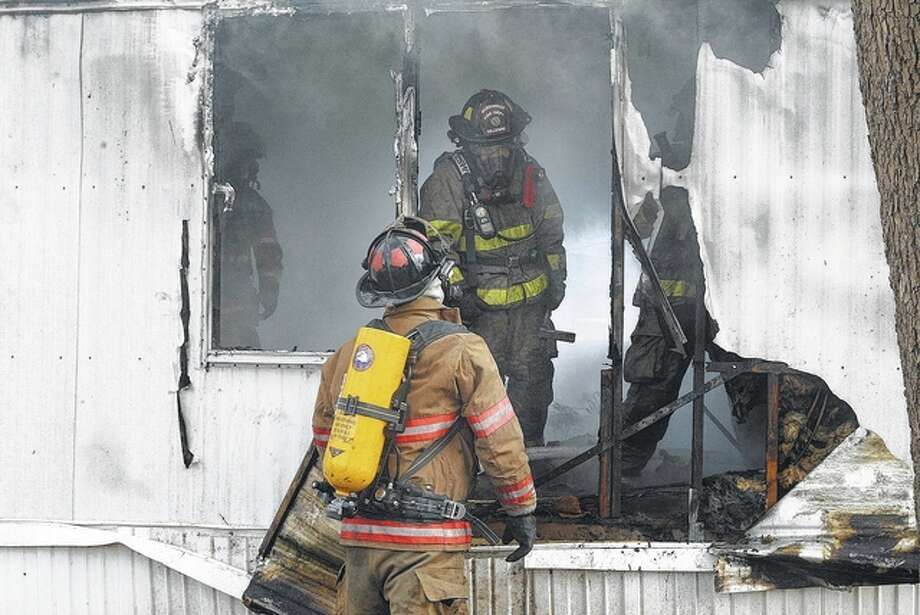 A South Jacksonville firefighter (foreground) and Jacksonville firefighter Brian Gillespie work Tuesday to extinguish a fire that destroyed a mobile home at 1033 E. Morton Ave., Lot 39. Jacksonville Fire Department Capt. Beth Kershaw said the fire is believed to have been caused by an electrical connection to a clothes dryer. Kershaw said no one was injured in the blaze. Photo: Greg Olson | Journal-Courier