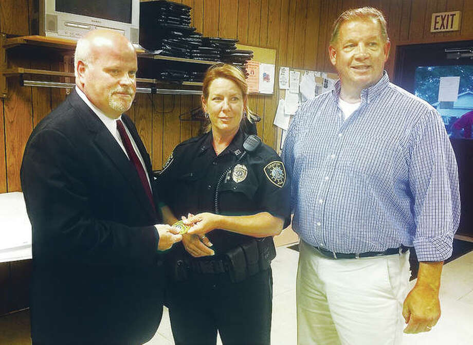 Grafton Police Chief Eric Spanton, left, receives his badge from interim Chief Peggy O'Neal, as Mayor Rick Eberlin looks on. Photo: Alex B. Heeb | The Telegraph