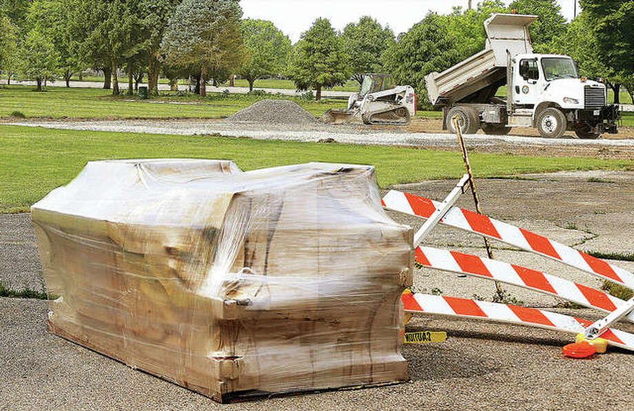 Shrink-wrapped pieces of the new all-inclusive playground equipment were sitting and ready to assemble Wednesday as an Alton city dump truck unloads rock for volunteer Rich Georgewitz to spread with his Bobcat tractor. Workers were out Wednesday preparing the playground site in Gordon Moore Park. Photo: John Badman | The Telegraph