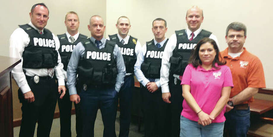 Lt. Jarrett Ford, chief of detectives at the Alton Police Department (rear center), and five Alton detectives wear new, tactical bullet-proof vests the department bought using a donation from Ed Sholar Jr., owner of Fast Eddie's Bon Air Tavern. At right are Bon-Air co-managers Danielle McCahill and Corey Bazzell. Photo: Linda N. Weller | The Telegraph