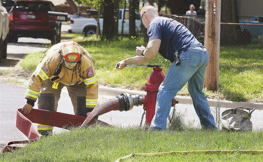Firefighters stretch out a supply line to a pumper truck Thursday and open the fire hydrant for a steady flow of water at the scene of a house fire at 401 Roosevelt Ave. in Wood River. Photo: John Badman | The Telegraph