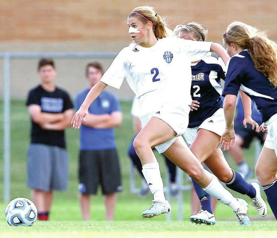 Marquette's Annabelle Copeland, left, breaks away from Rochester defenders in the 2015 Class 1A Springfield Super-sectional. Now a senior, Copeland and her teammates will renew their postseason rivalry with Rochester Friday in the title game of the Jacksonville 2A Regional. Photo: Telegraph File Photo