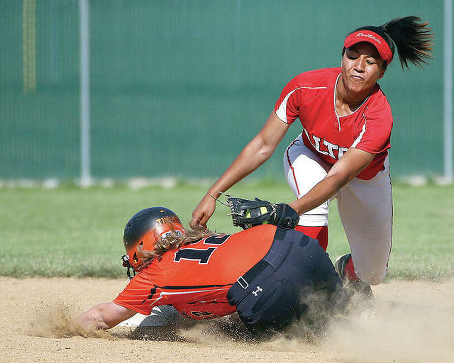 Edwardsville's Brooke Webber slides into second base, avoiding the tag of Alton's Savannah Fisher during Thursday's SWC game at Alton High School. Photo: Billy Hurst | For The Telegraph