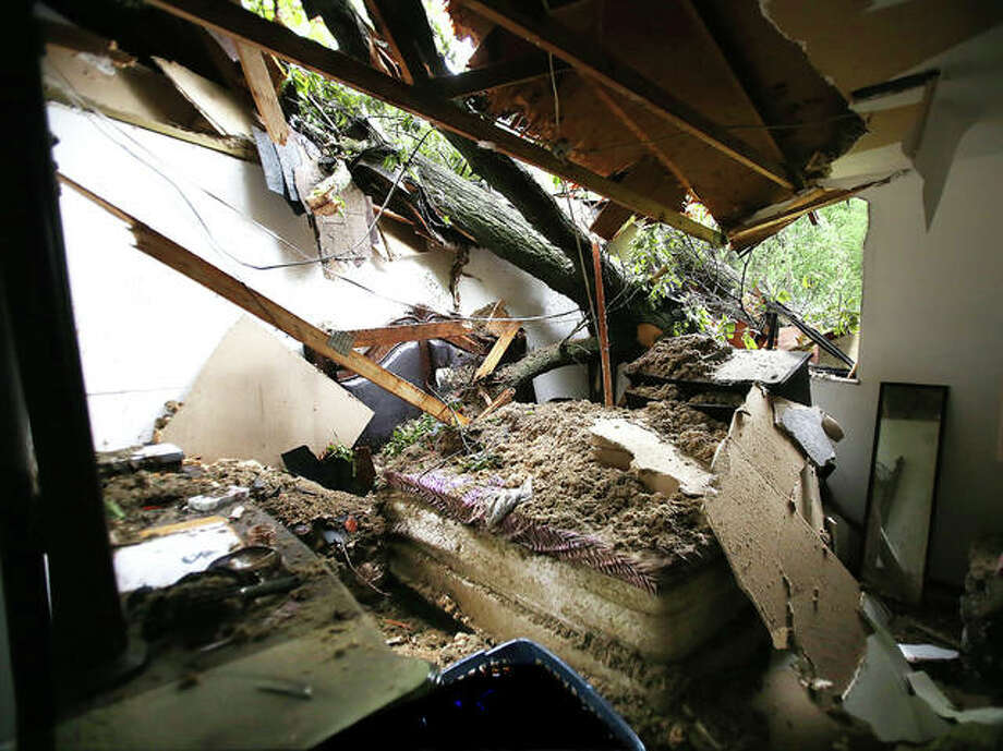 A tree went through the roof of an upstairs apartment Friday morning at 3301 Myrle Street in Alton during the storm and landed on the bed where a woman was reportedly sleeping. Photo: John Badman | The Telegraph