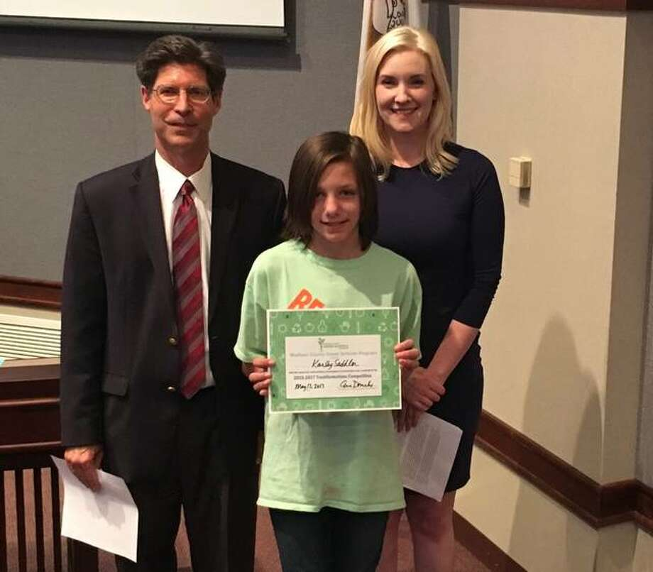 Madison County Board Chairman Kurt Prenzler and Resource Education Program Coordinator Eve Drueke present Karley Saddler of Columbus Elementary School in Edwardsville with a certificate of recognition for the Trashformation competition. Photo: For The Telegraph