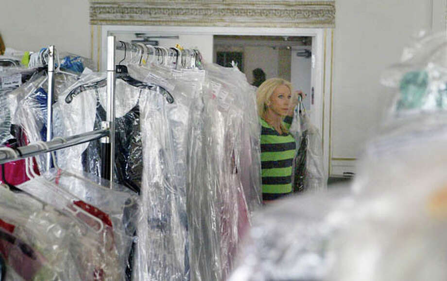 Sarah Hautala, general manager of radio stations WJIL-WJVO, carries an armload of dresses into the ballroom at Hamilton's in Jacksonville on Saturday in preparation for today's Bridal and Formal Encore. Gently used wedding and formal clothing has been taken on consignment for the event, including homecoming, prom, wedding and mother-of-the-bride dresses, as well as special-occasion attire such as shoes, jewelry and decor. Doors will open at 11 a.m. today for the event. There is a $1 admission charge, which goes to Prairieland United Way. Hamilton's is at 110 N. East St. Photo: David C.L. Bauer | Journal-Courier