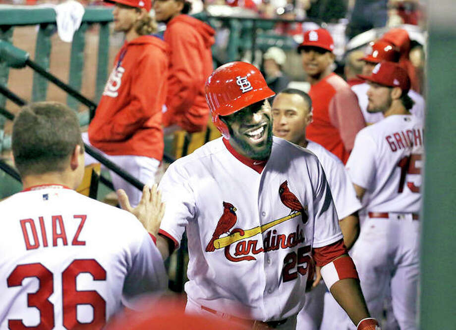 The Cardinals' Dexter Fowler is congratulated by teammates in the dugout after hitting a three-run home run in the seventh inning Friday night against the San Francisco Giants at Busch Stadium in St. Louis. Photo: AP