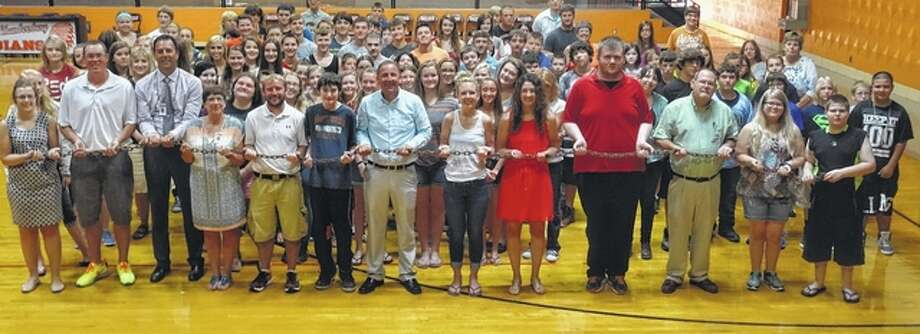 "Meredosia-Chambersburg Junior-Senior High School students, faculty and staff hold a log chain that represents the ""Links of Strength"" that people share with each other. Meredosia-Chambersburg special education teacher Cary Knox (center in blue shirt) has written a series of Links of Strength expressions that he has shared with students and will soon be available at Kirlin's Hallmark stores as wall art. Photo: Courtesy Of Cary Knox"
