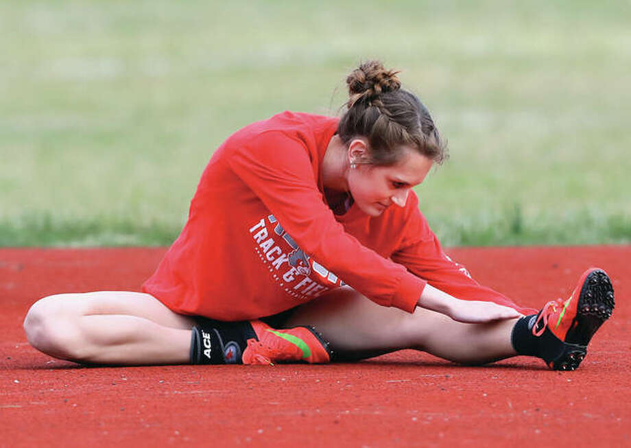 Alton's Katie Mans stretches before competing in the high jump during the Southwestern Illinois Relays on March 24 at Edwardsville. Mans was in Charleston on Saturday and earned her third Class 3A state medal with a third-place finish in the high jump. Photo: Billy Hurst / For The Telegraph