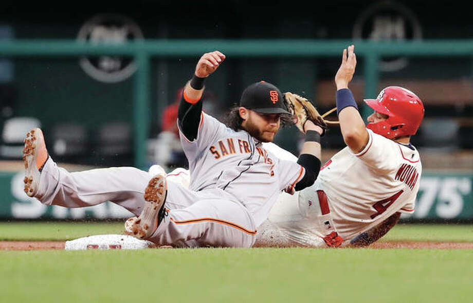 The Cardinals' Yadier Molina (right) is tagged out by Giants shortstop Brandon Crawford while trying to steal second during the second inning Saturday night at Busch Stadium. Photo: Associated Press