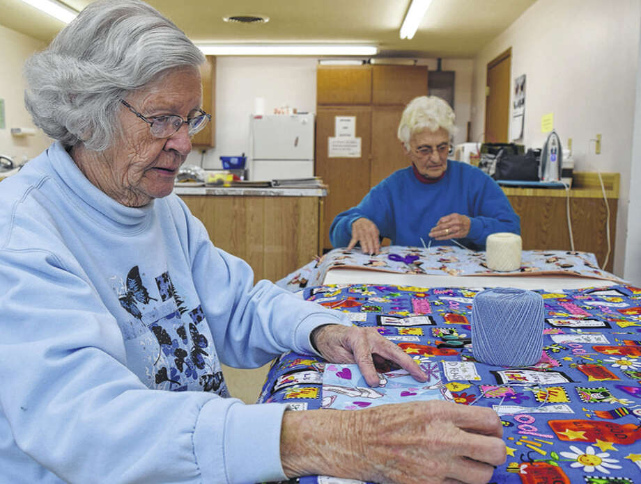 Volunteers Lois Stice of Winchester and Marilyn Scott of Winchester get to work preparing blankets for children Tuesday at the Nimrod Funk 4H and Community Building in Winchester. Photo: Nick Draper | Journal-Courier