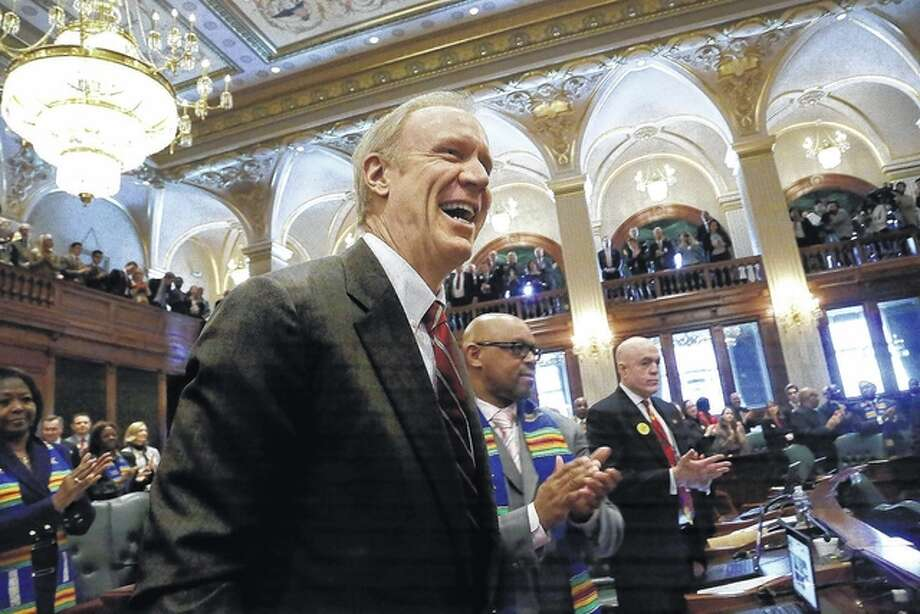 Seth Perlman | AP Lawmakers applaud Gov. Bruce Rauner before he delivers his State of the Budget address last year in Springfield. Rauner takes pride in not being like any previous governors, either on matters of style or substance. After his first year in office, Rauner is starting 2016 with signs that the strangest may be yet to come. He is talking tougher than ever about his adversaries and is raising the specter of growing chaos, including public employee strikes, layoffs and more shutdowns in state services.