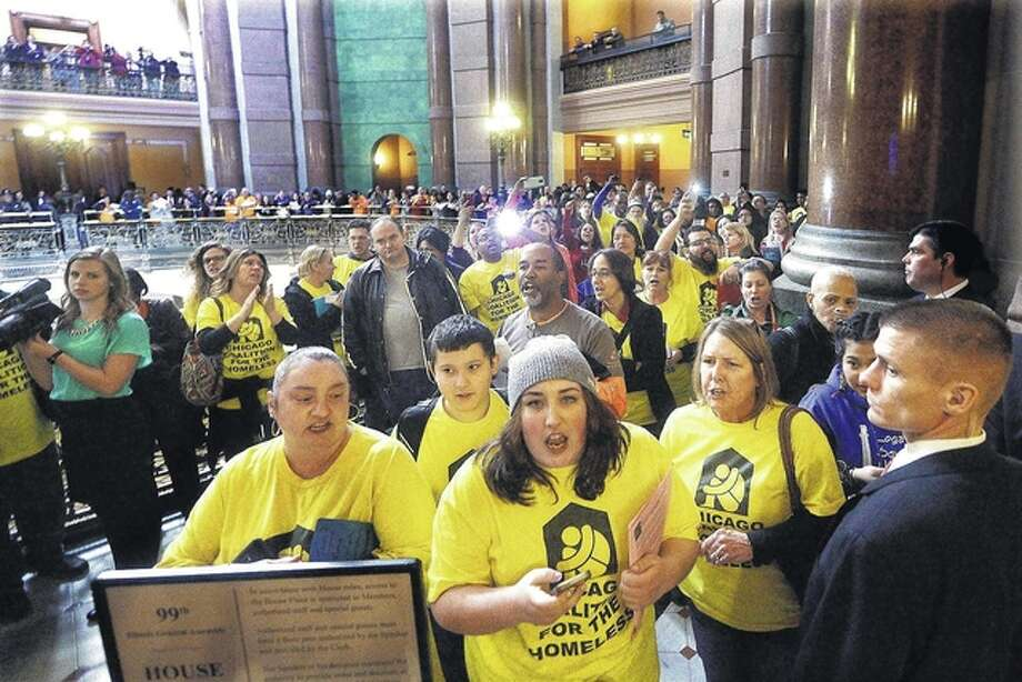 Seth Perlman / AP Various groups and organizations protest against budget cuts and rally in favor of passing a state budget outside the House chamber while Gov. Bruce Rauner delivers his State of the State address Wednesday.