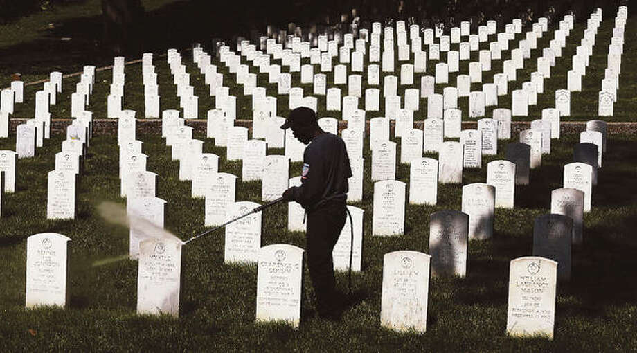 John Badman|The Telegraph An employee of BOCO Contracting & Construction, LLC, a Brighton veteran owned business, is silhouetted Thursday against the white headstones in the Alton National Cemetery on Pearl Street. A crew was power washing the headstones to clean them in preparation for Memorial Day on May 29th. The headstones are washed twice a year but Memorial Day is a day to honor veterans. The Alton National Cemetery has a Revolutionary War veteran, Civil War veterans and many vets from World Wars I and II.