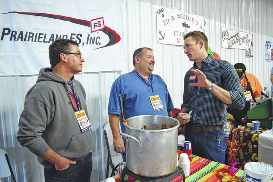 The Prairieland FS chili cook-off team of Ken Devlin of Jacksonville (from left) and Dick Pitchford of Waverly speak with Republican state Senate candidate Bryce Benton of Springfield Saturday at the 19th annual Winchester EMS Chili Cook-off in Winchester. Photo: Greg Olson | Journal-Courier