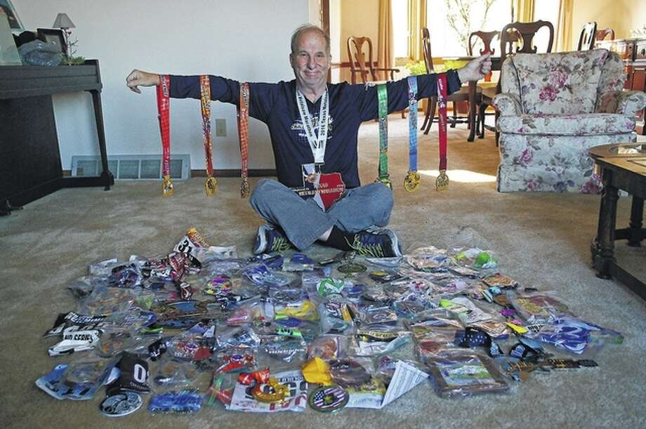 Jim Alexander of Jacksonville displays the memorabilia from the 100 marathons he has run in the past 10 years, including a Texas-sized medal from the Texas Marathon around his neck and six medals from Disney World, which was the location for marathon number 100. Photo: David Blanchette | Journal-Courier