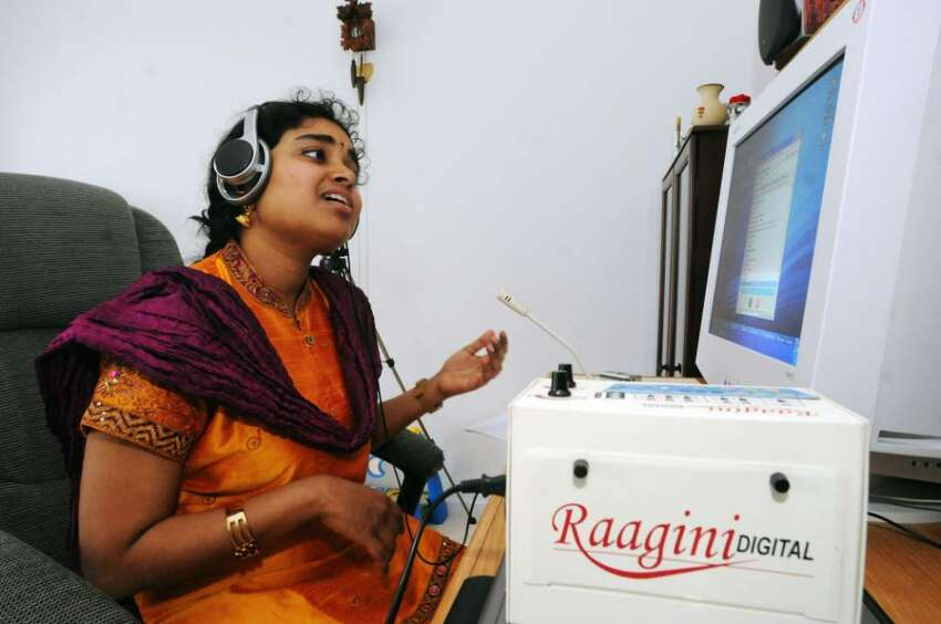 Indian musician and teacher, Vidya Subramanian, sings with an electronic tambura while doing a pod-cast on the computer at her home in Clifton Park, N.Y., in April of 2009. (James Goolsby/Times Union)
