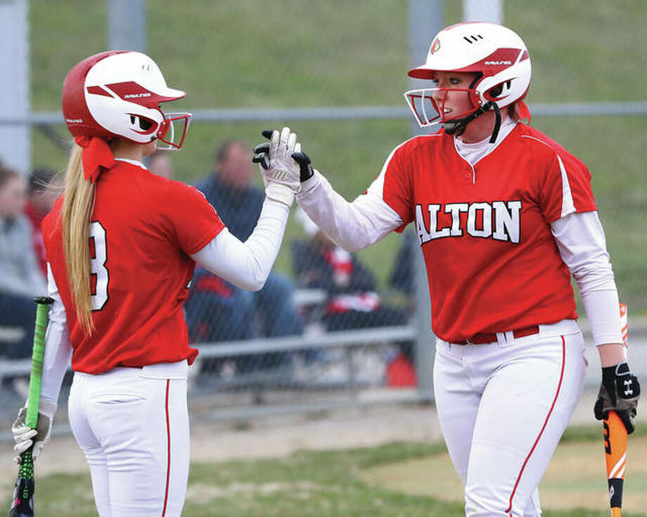 Alton's Tomi Dublo (right) is greeted by teammate Sydney Hartman after scoring a run during a game earlier this season at Alton High in Godfrey. The Redbirds' softball season ended at 22-11 on Tuesday night with a Class 4A regional loss in Springfield. Photo: Billy Hurst / For The Telegraph