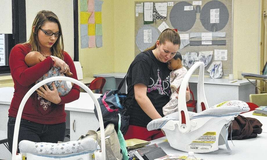 """Pittsfield High School students Margaret Wright (left) and Lexus Ham tend to their """"babies"""" as part of a parenting class. Photo: Jeff Ruzicka   Journal-Courier"""