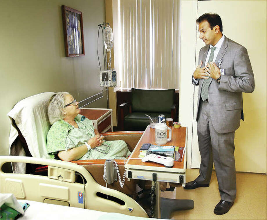 """OSF Saint Anthony's Health Center patient Kimberly Haymaker, 53, left, chats with Ajay Pathak, president and CEO of administration, recently as he conducts """"rounding"""" at the hospital. Rounding is when health center leaders ask patients about the quality of their care, treatment and well-being. The leader checks the patient's care board, takes notes and asks if there is any way their stay could have been improved. Haymaker, of Granite City, was very satisfied with her treatment at the hospital. Photo: John Badman