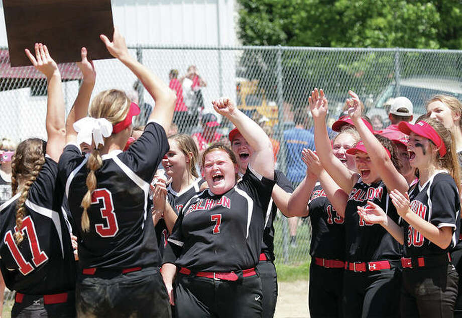 Calhoun seniors Grace Baalman (3) and Abby Baalman (17) bring the Class 1A sectional plaque back to Macy Margherio (7) and their teammates after the Warriors beat Camp Point Central 1-0 in eight innings Saturday in Hardin. Photo: James B. Ritter / For The Telegraph