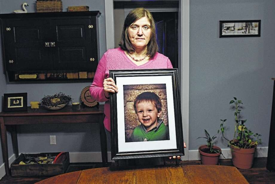 John Beale | AP Hollie Ayers poses with a photograph of her late son at her home in Bedford, Pennsylvania. Michael was 2 when he was shot and killed in front of her by her abusive ex-husband in 2013. Ayers was shot in the face and the leg, and her ex-husband killed himself after the rampage. More than a dozen states over the past two years have strengthened laws meant to keep firearms out of the hands of domestic abusers, a rare area of consensus in the nation's highly polarized debate over guns.