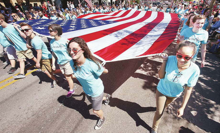 Members of the Christian musical group Encounter carry the large American flag up Washington Avenue in Alton Monday during the 150th annual Alton Memorial Day Parade. Thousands turned out under clear skies to watch the longest consecutive running Memorial Day parade in the nation. Photo: John Badman|The Telegraph