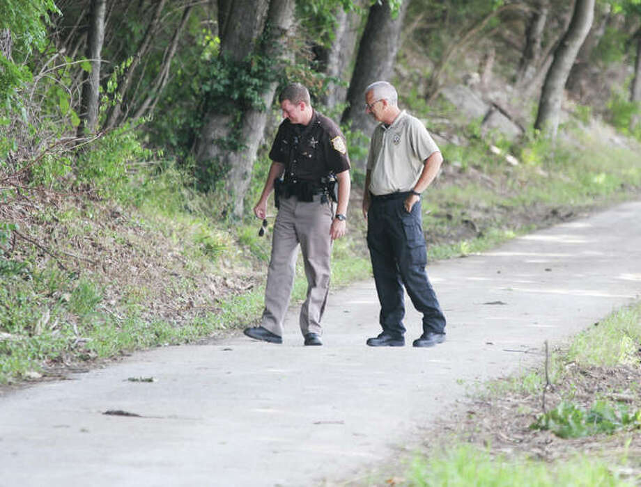 Madison County Sheriff's Deputy Jason Thatcher and Madison County Coroner's Office Chief Investigator Kelly Rogers looks for evidence along the Vadalabene Trail on the Great River Road Tuesday morning following a fatal accident late Monday. Photo: Scott Cousins | The Telegraph