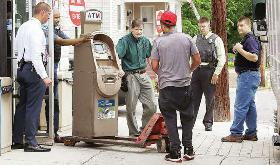 In this May 23 photo, Alton Police detectives, agents of the U.S. Department of the Treasury's Internal Revenue Service, and a locksmith remove an automated teller machine from the Cowboy Quick Stop Inc., 835 Central Ave., Alton, after closing the store for about an hour. Photo: John Badman | The Telegraph