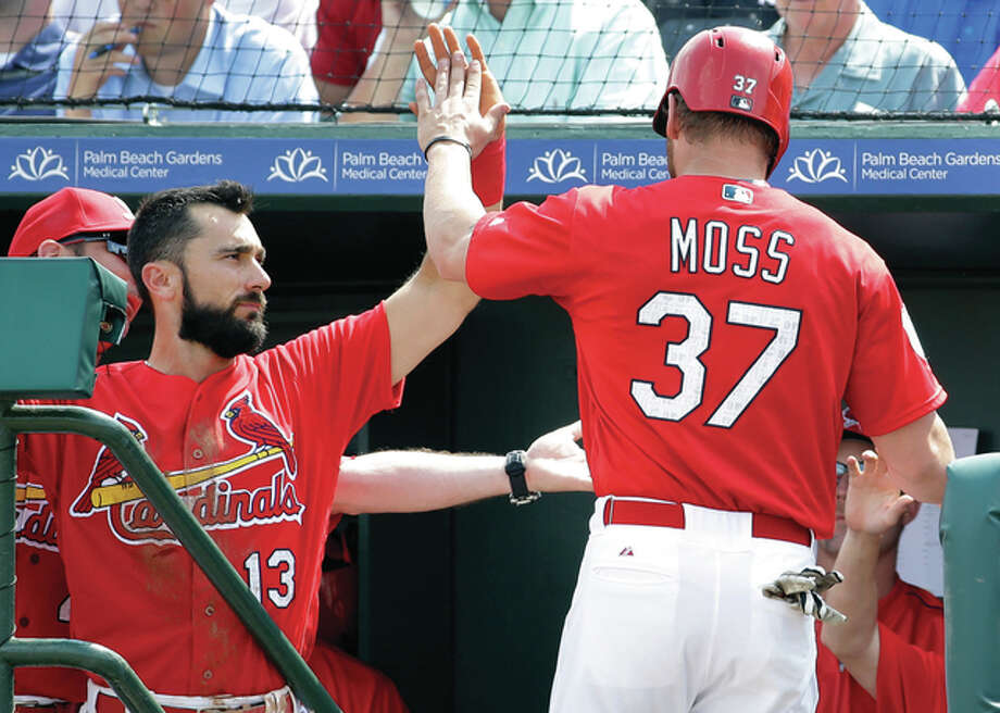 The Cardinals' Brandon Moss (37) is congratulated by teammate Matt Carpenter after scoring on a double by Carlos Peguero during the first inning of an exhibition spring training game against the Miami Marlins on Thursday in Jupiter, Fla. The Cardinals won 4-3. Photo: Associated Press