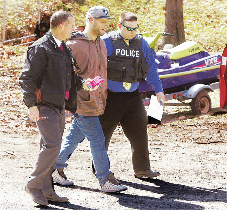 Alton Police officers escort Mark Kuni, 37, of Cottage Hills to the Alton City Jail Wednesday during a Nuisance Abatement Task Force stop at a house at the corner of Halliburton and Funke streets in Alton. Police said Kuni is facing a charge of driving on a suspended license. Police said the residence was the subject of several complaints to the city about junk and trash. Police had three vehicles towed from the property.