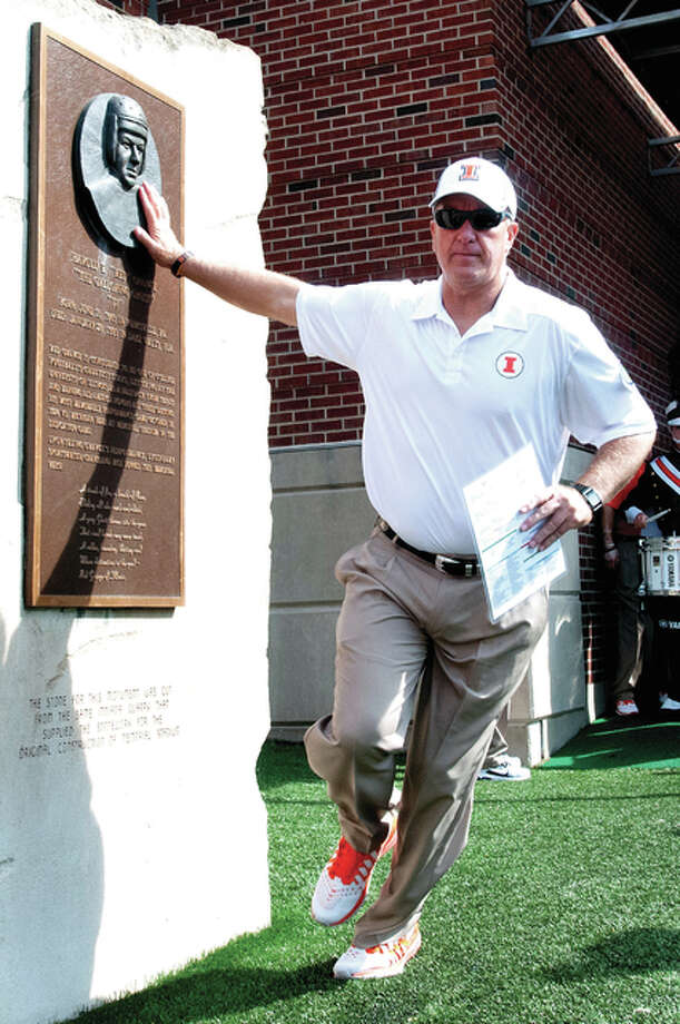 Bill Cubit touches Red Grange Rock for luck prior to a 2013 game when he served as offensive coordinator for Illinois. Cubit is now the head coach of the Illini. Photo: File Photo