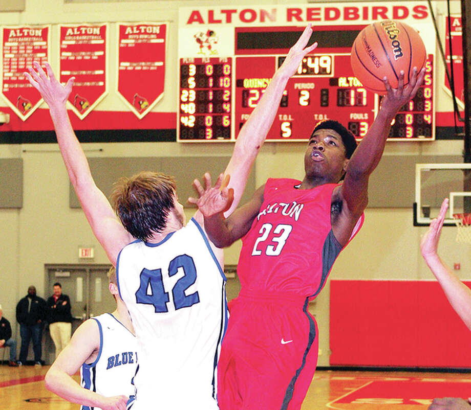 Alton's Kevin Caldwell Jr. goes around Quincy's Parker Bland for a basket Friday night in the Class 4A Regional championship game at Alton High. Photo: James B. Ritter | For The Telegraph