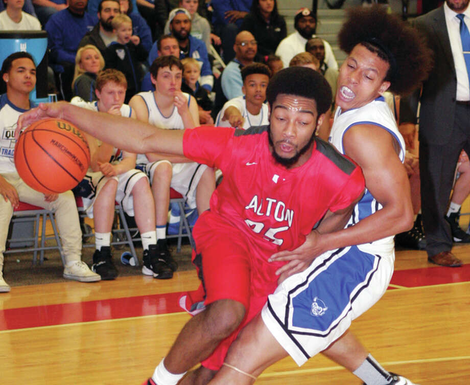 Alton's Maurice Edwards (left) drives past Quincy's Deven Smith and draws a foul during the championship game of the Alton Class 4A Regional on Friday night at Alton High in Godfrey. Photo: James B. Ritter / For The Telegraph