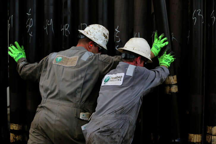 Floor hands move casings in Atascosa County. U.S. oil production rose to a record high in January.