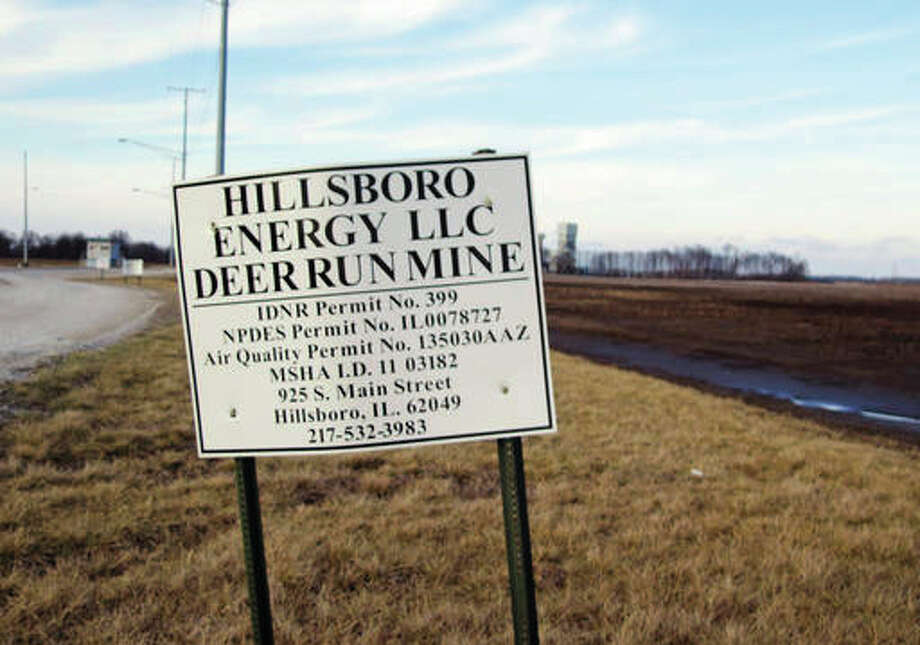 This Feb. 5, file photo shows a sign leading to the Deer Run coal mine, background, where a smoldering underground fire led owner Hillsboro Energy LLC, a subsidiary of Foresight Energy, to indefinitely shut down the southern Illinois facility near Hillsboro, Illinois. As the mine owner seeks an expansion on a site unaffected by the fire, the state Attorney General's Office is considering legal action against the Illinois Department of Natural Resources for what prosecutors call a failure to follow the terms of a court-brokered plan to toughen oversight of the mine permit process. Photo: (AP Photo/Alan Scher Zagier, File)