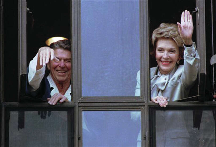In this July 18, 1985, file photo, President Ronald Reagan and his wife, Nancy, wave from windows of his hospital room at the Navy Medical Center in Bethesda, Maryland. The former first lady has died at 94, The Associated Press confirmed Sunday, March 6.