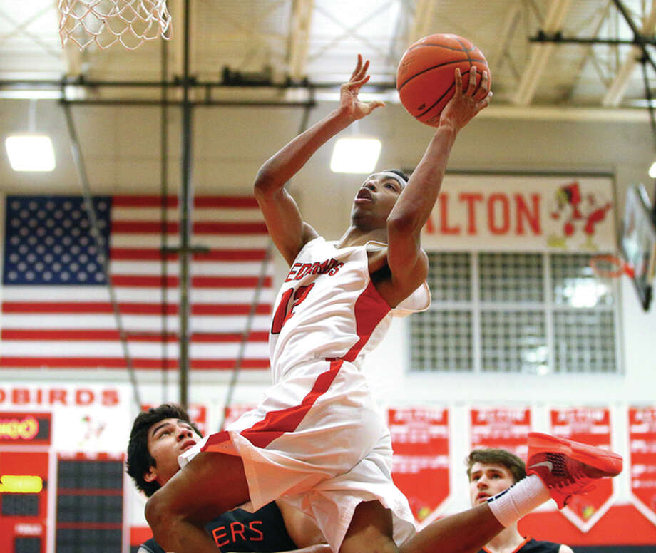 Alton's Tre Smith (top) beats Edwardsville's AJ Epenesa (left) and Oliver Stephen (right) to the rim during a Southwestern Conference game Feb. 19 at Alton High in Godfrey. The Redbirds and Tigers meet for a third time Tuesday in the semifinals of the Collinsville Class 4A Sectional at Fletcher Gym. Photo: Billy Hurst / For The Telegraph