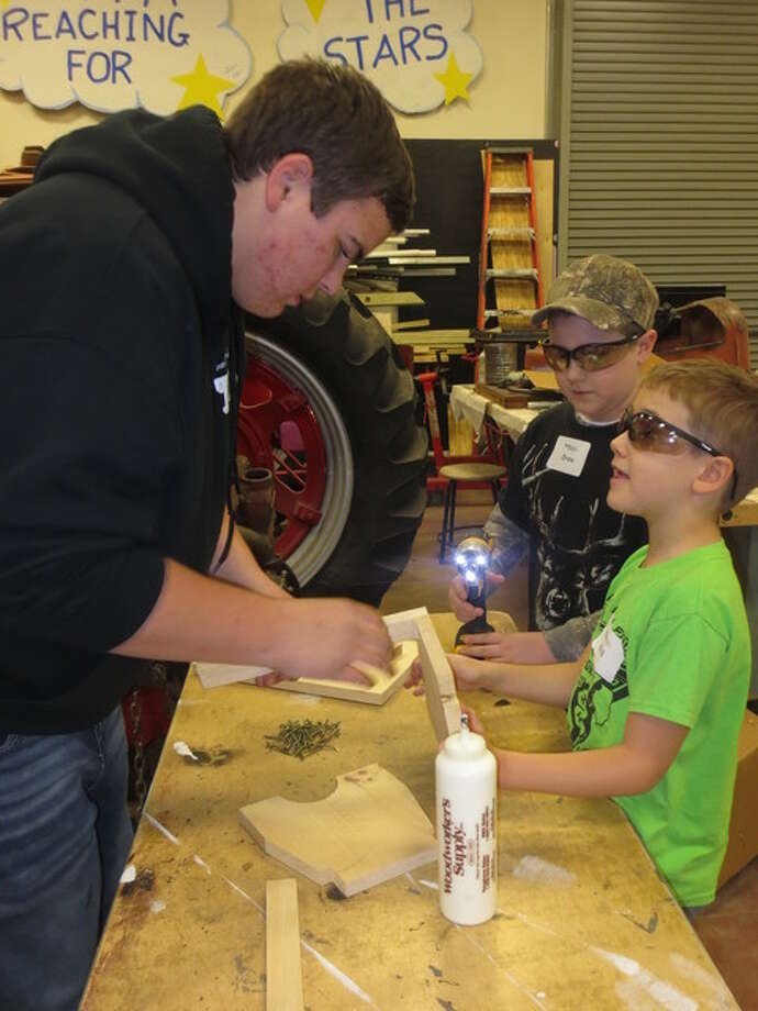 """Bubs"" is shown helping Will Pelletier and Drew Goetz assemble their step stools, which was a combination of glue and screws."