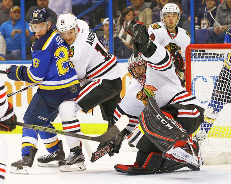 Chicago Blackhawks goalie Corey Crawford makes a save as teammate Artem Anisimov (15) and the Blues' Paul Stastny (26) look for the rebound Wednesday night in St. Louis. Photo: Billy Hurst | AP Photo