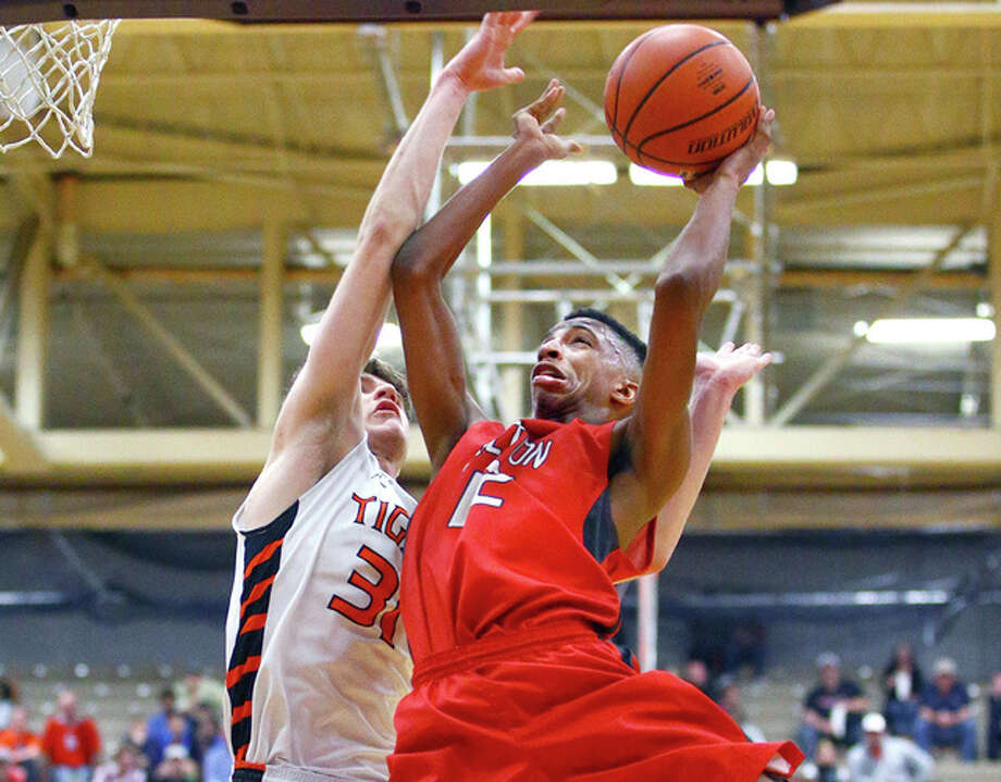 Alton's Tre Smith (12) puts up a shot in the lane and is fouled by Edwardsville's Oliver Stephen (31) in Tuesday's 4A sectional semifinal win in Collinsville. Alton won the game 63-59 and will face East Moline at 7 p.m. Friday for the sectional championship. Photo: Billy Hurst | For The Telegraph