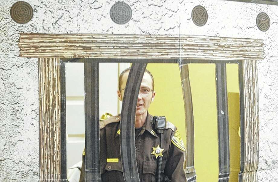 """Cass County Sheriff's Capt. Devron Ohrn gets locked up during a fundraiser Tuesday for the Muscular Dystrophy Association. Ohrn, along with others, raised money for the association to get out of """"jail."""" Photo: Samantha McDaniel-Ogletree 