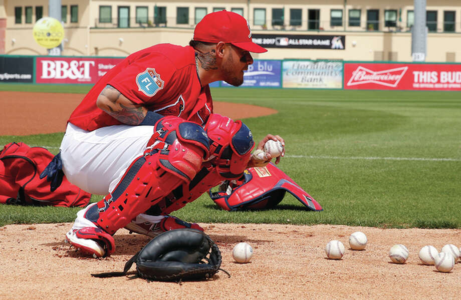 Cardinals catcher Yadier Molina practices catching the ball with an injured thumb before Friday's spring training game against the Atlanta Braves in Jupiter, Fla.