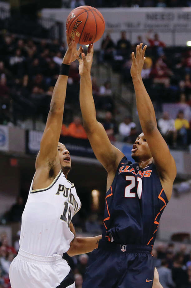Purdue's Vince Edwards (left) blocks a shot by Illinois' Malcolm Hill on Friday in the quarterfinals at the Big Ten Conference tournament in Indianapolis. Photo: Associated Press