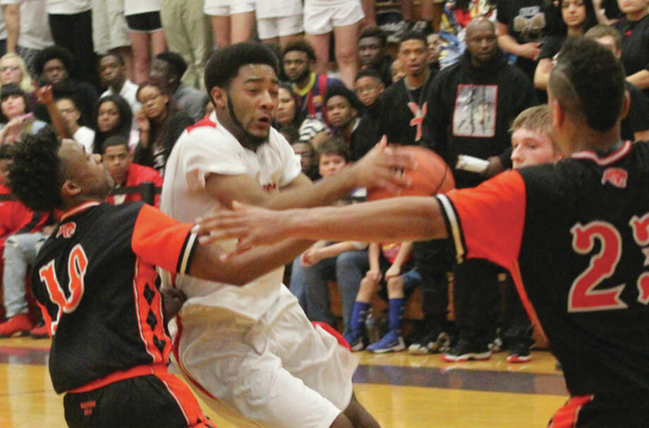 Alton's Maurice Edwards (middle) drives into East Moline United's zone during Friday night's championship game of the Collinsville Class 4A Sectional at Fletcher Gym Photo: Scott Cousins / For The Telegraph