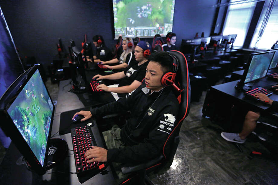 "In this Sept. 23, 2014 file photo, Robert Morris University Illinois freshmen from left, Sondra Burrows, Brian Rodonis and Alex Chapman practice playing the video game ""League of Legends"" with their collegiate teammates at their on-campus training facility in Chicago. Several experts credit Riot Games, the company behind popular online game ""League of Legends,"" for building a system that aims to improve the culture of the game and change player behavior. If a player is punished, the company's system tells them why they were reported and shows them the specific comments that other players didn't like."